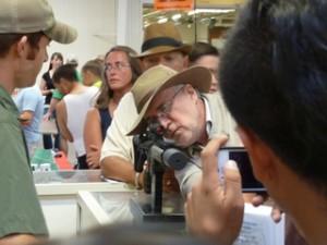 Javier Sicilia looks down gunsight at Albuquerque gun show during Caravan for Peace. Summer 2013 Photo Credit: Global Exchange