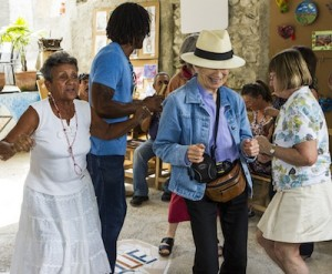 Catherine Sagan (middle with hat) dances at the Muraleando community project in Havana