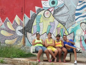 Teenagers in front of a Muraleando mural.