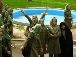 School girl in Iran waves peace sign.