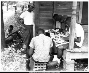 Students-in-a-Freedom-School-class-taught-by-volunteer-Arthur-Reese-read-copies-of-Ebony-magazine-on-the-front-porch-of-a-house-in-Hattiesburg-Mississippi-during-Freedom-Summer-1964.